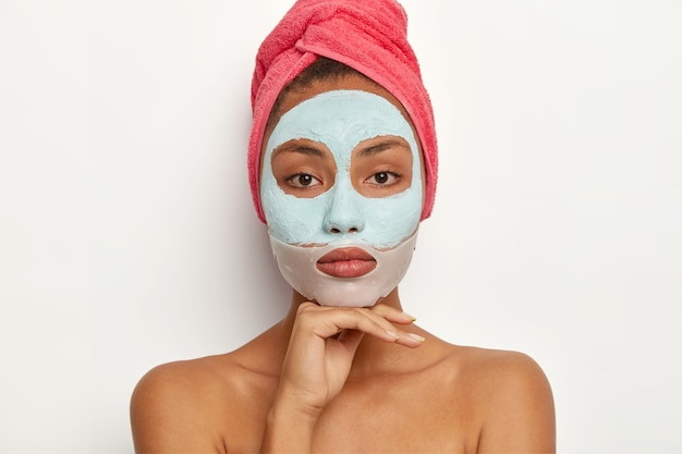 Calm young female model enjoys daily skincare regime, applies soothing mask on face, reduces surface shine, exfoliates blackheads, has wrapped towel on head, touches chin gently, looks
