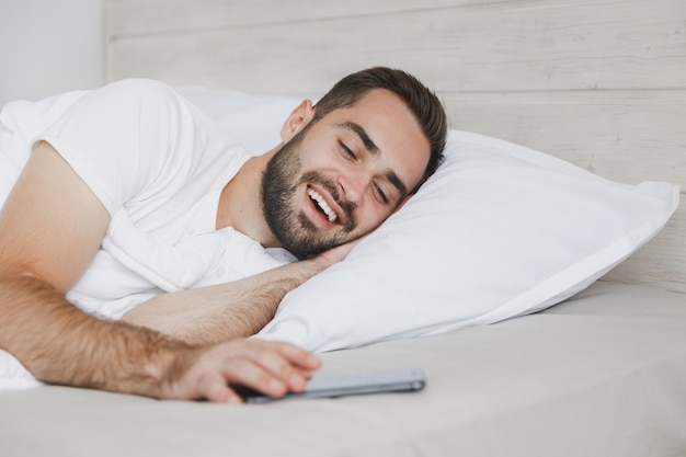 Calm young handsome bearded man lying in bed with white sheet pillow blanket in bedroom at home