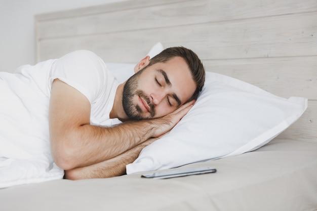 Спокойный молодой красивый бородатый мужчина, лежащий в постели с белым листовым одеялом в спальне дома
