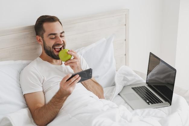집에서 침실에 흰색 시트 베개 담요와 침대에 누워 진정 젊은 잘 생긴 수염 난된 남자