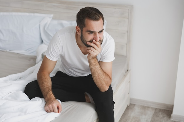 Calm young handsome bearded man sitting in bed with white sheet pillow blanket in bedroom at home