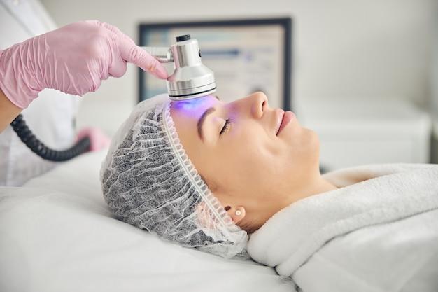 Спокойная барышня в марлевой шапочке лежит с закрытыми глазами во время терапии пурпурным светом.