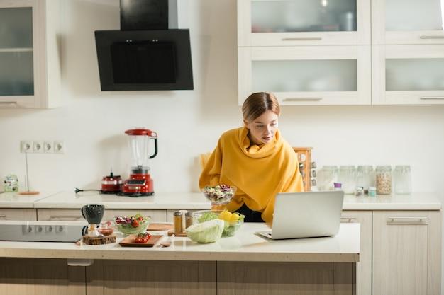 Спокойная барышня, внимательно смотрящая на экран своего современного ноутбука на кухонном столе, стоя со стеклянной миской свежего салата в руке