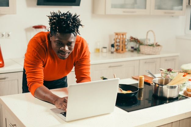 フライパンを横に置いてキッチンにいる間、現代のノートパソコンの画面を注意深く見ている穏やかな若い男