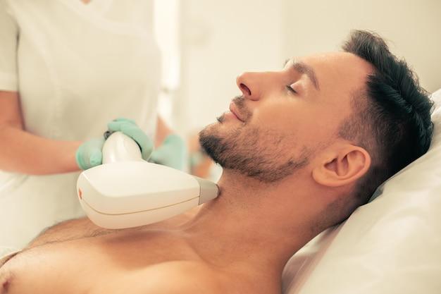 Спокойный молодой человек лежит с закрытыми глазами и косметолог в резиновых перчатках удаляет волосы с помощью лазерного инструмента