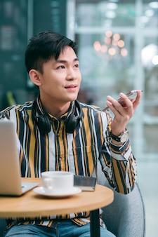 Спокойный молодой человек сидит за столом и смотрит в сторону, давая задание своему голосовому помощнику