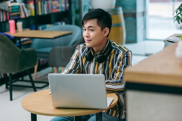 Спокойный молодой человек сидит за столом с современным ноутбуком и с улыбкой смотрит в сторону