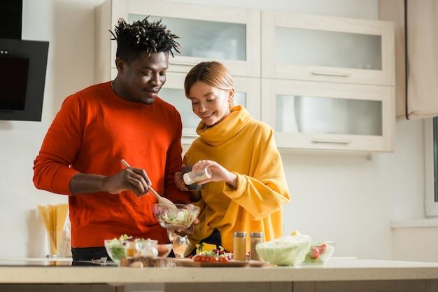 Спокойный молодой человек, стоящий на кухне с миской салата в руках и улыбающейся подругой, добавляющей ему соли