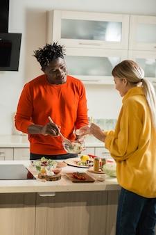 Спокойный молодой человек стоит на кухне с салатом в руках и улыбается, пока его девушка добавляет соль в еду