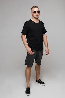 ポケットに手を入れて灰色の背景に立っている穏やかな若い男。彼のtシャツとショートパンツ。ファッションコンセプト