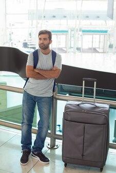 荷物の近くに立って交差腕を持つ穏やかな若い男