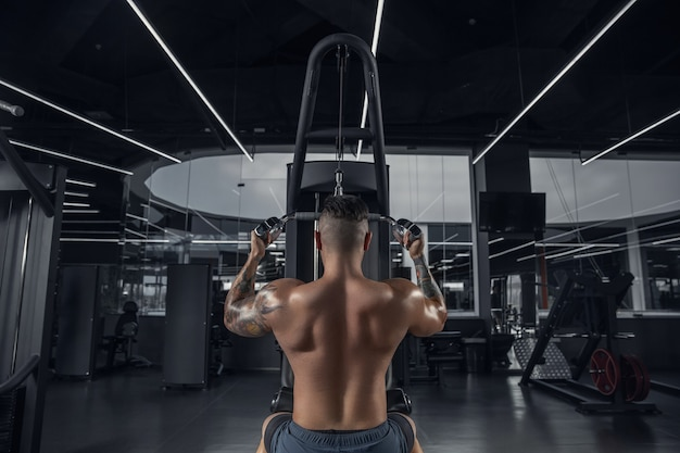 落ち着いたウェイトを使ってジムで練習する若い筋肉質の白人アスリート。筋力トレーニングを行う男性モデル、上半身のトレーニング。健康、健康的なライフ スタイル、ボディービルのコンセプト。