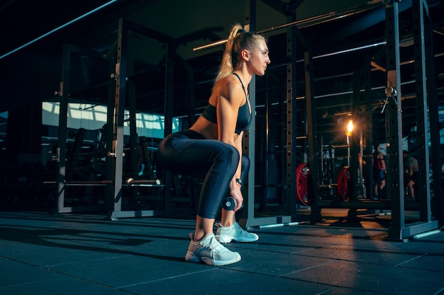 고요한. 무게와 체육관에서 연습 젊은 근육 백인 여자. 강도 운동을하는 운동 여성 모델, 그녀의 상체, 하체 훈련. 웰빙, 건강한 라이프 스타일, 보디 빌딩.