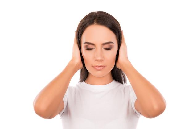 Спокойная молодая женщина закрыла уши и пытается сосредоточиться
