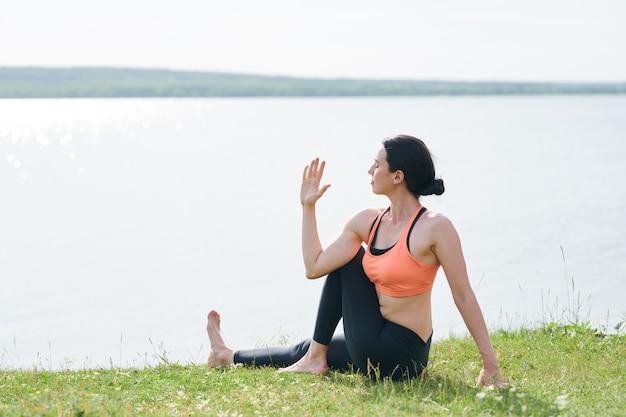湖の芝生の上に座って、屋外で背骨をねじりながら目を閉じておくスポーツ服の穏やかな若い女性