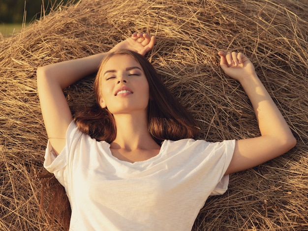 穏やかな若い女性は干し草の山でリラックスしています。美しい穏やかな女の子は自然にあります。長い茶色の髪の幸せなブルネットの少女。自然のかわいいモデルの肖像画。リラックスした夏の時間。