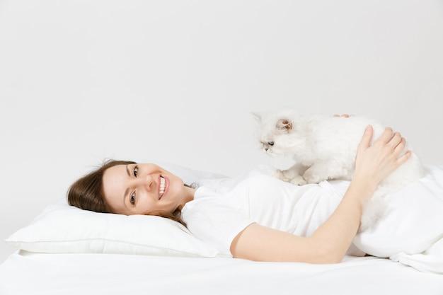 白いかわいいペルシャの銀のチンチラ猫、シーツ、枕、白い壁に毛布と一緒にベッドに横たわっている穏やかな若い女性