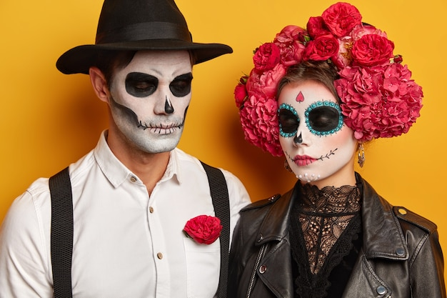 Calm young woman and man wears skull makeup, female in beautiful floral wreath, dressed in halloween holiday costumes, keep eyes shut, isolated over yellow studio background.