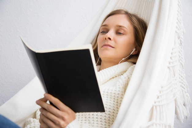 Calm young woman reading book and listening to music