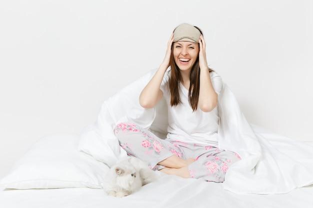 白い壁で隔離の目の睡眠マスクとベッドに座っている穏やかな若い女性