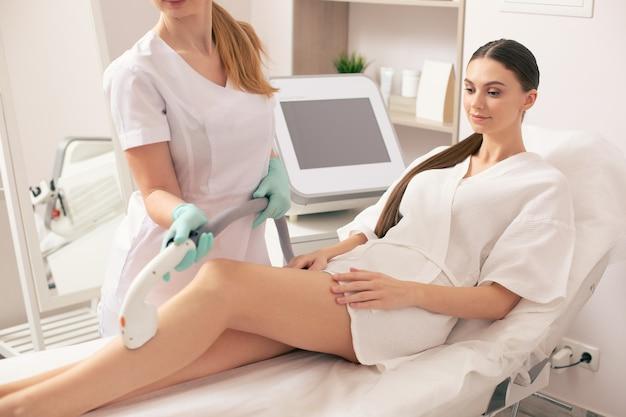 Спокойная молодая женщина сидит на медицинской кушетке в коротком халате и улыбается во время лазерной эпиляции с помощью вакуумного отсоса