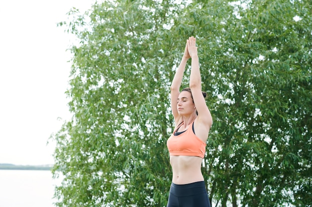 Calm young woman in sports bra concentrated on yoga practice raising hands up and keeping eyes closed while doing relaxation exercise
