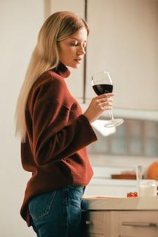 Спокойная молодая женщина, стоящая одна на кухне и внимательно смотрящая на красное вино в своем бокале