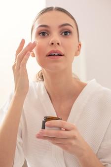 肌にフェイシャルクリームを塗っている間、鏡をじっくりと見つめるナチュラルメイクの落ち着いた若い女性