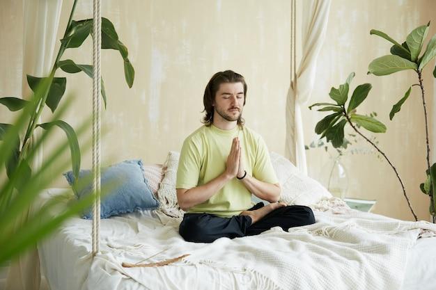 Успокоенный мужчина в йога-сане на кровати и намасте, умиротворяющая чашка для медитации, концентрирующаяся дома утром