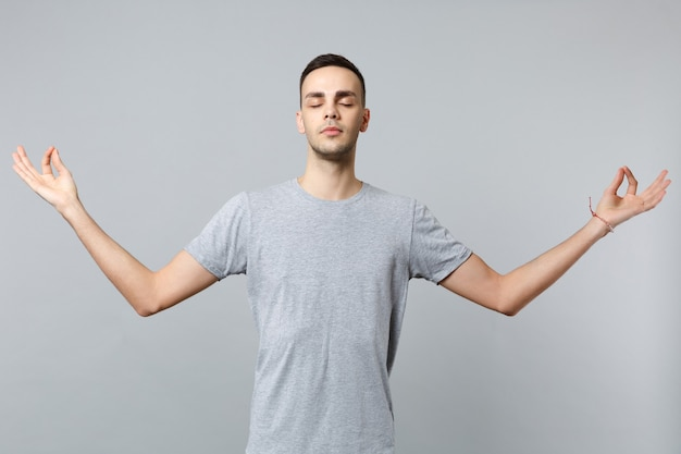目を閉じてカジュアルな服を着て落ち着いた若い男は、瞑想をリラックスしてヨガのジェスチャーで手を握ります