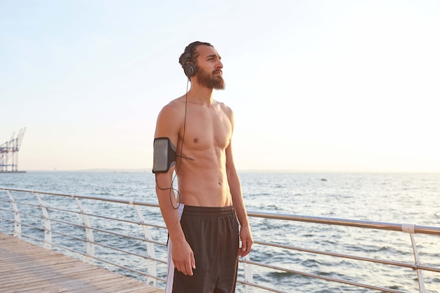 落ち着いた若い魅力的なあごひげを生やした男は、海辺で極端なスポーツをし、ジョギングの後に休憩し、海を見て、ヘッドフォンで歌を聴き、健康的なアクティブなライフスタイルを導きます。フィットネス男性モデル。