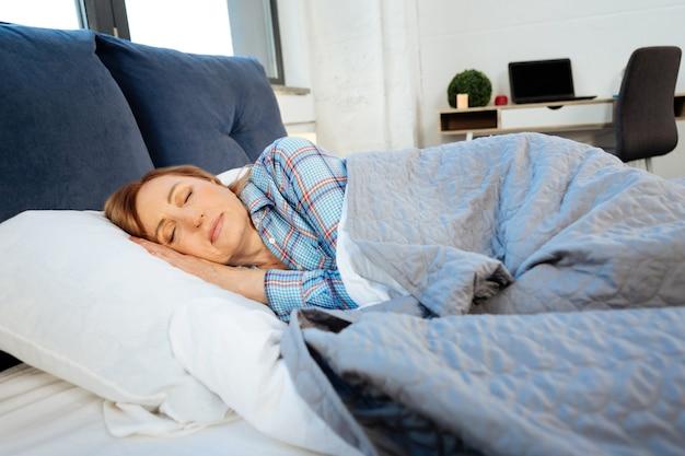 Спокойно врет. мирная женщина средних лет спит в своей постели одна, укрытая синим одеялом