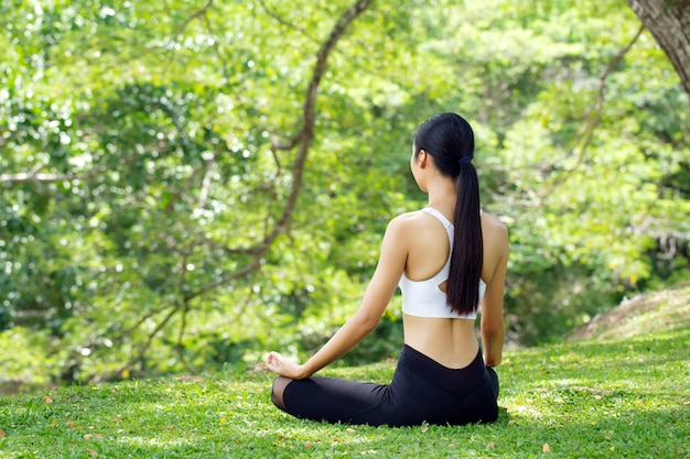 평온함과 휴식, 아시아 여성들은 야외 공원에서 요가를 연습하면서 명상을합니다. 자유 concept.woman 행복. 몸매 그림 건강한 삶