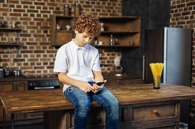 평온함과 평온함. 나무 주방 섬에 앉아 스마트 폰 화면에 집중하면서 재생 목록에서 음악을 선택하는 초반 밤나무 머리 소년.