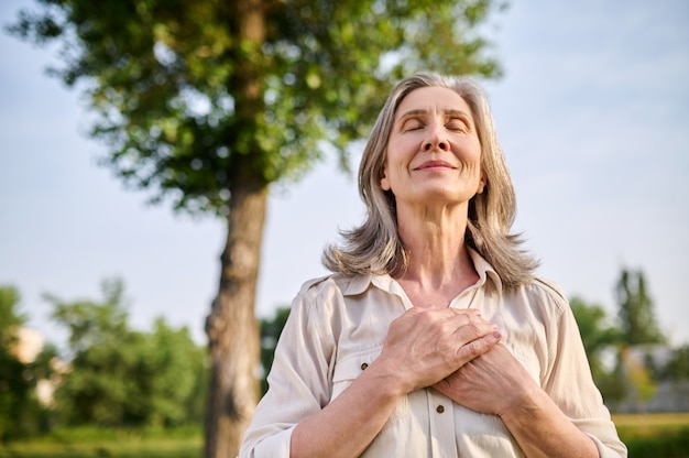 Calmness. happy adult smiling woman with closed eyes folded hands on her chest in summer park
