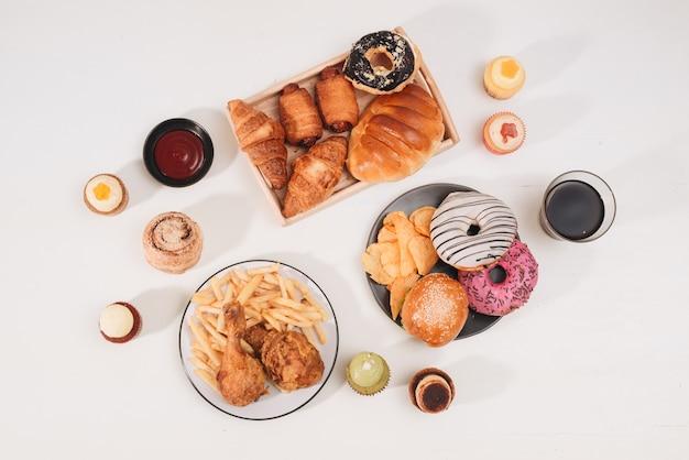 Калорийный бургер с картофелем фри, люди едят за столиком в кафе, нездоровый обед