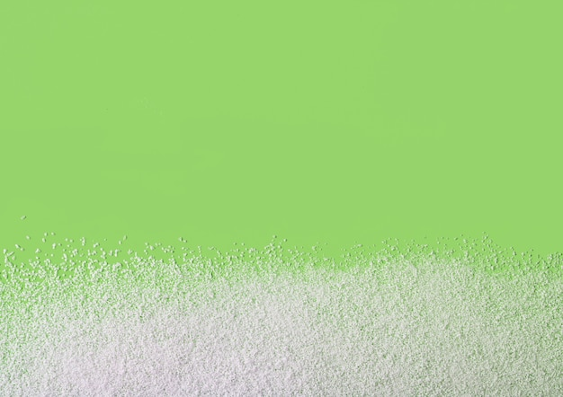Бескалорийный порошок подсластителя, рассыпанный на зеленом фоне