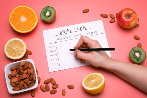 Calories control meal plan diet and weight loss concept top view of hand filling meal plan