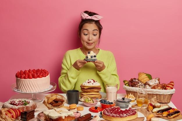 칼로리 음식, 유혹 및 잃어버린 체중 개념. 사랑스러운 외모를 가진 한국 소녀는 식욕이 좋은 달콤한 머핀을보고 맛있는 간식을 즐기고 분홍색 배경에 포즈를 취합니다.