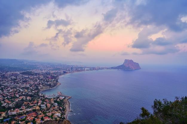 日没の曇りの日に海の真ん中に岩があるカルペアリカンテ湾。