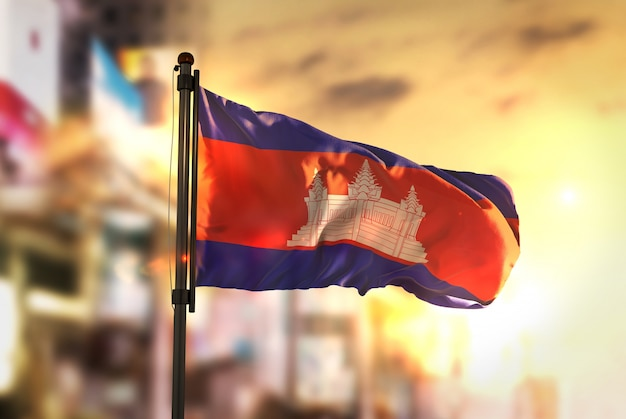 Cambodia flag against city blurred background at sunrise backlight