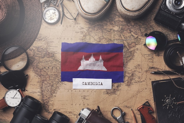 Cambodia flag between traveler's accessories on old vintage map. overhead shot