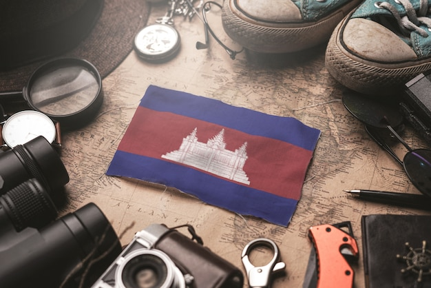 Cambodia flag between traveler's accessories on old vintage map. tourist destination concept.