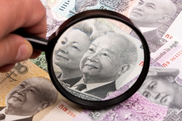 Cambodian riel in a magnifying glass a business background