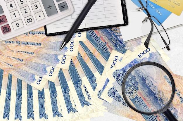 Камбоджийские банкноты риелей и калькулятор с очками и ручкой