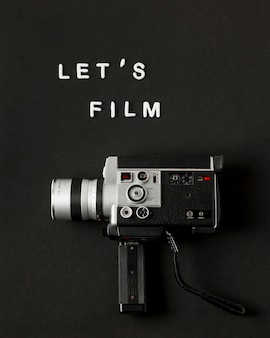 Camcorder camera with text let's film on black background