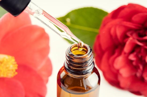 椿のエッセンシャルオイル。ピペット、琥珀色のボトル、椿の花のクローズアップ。薬草