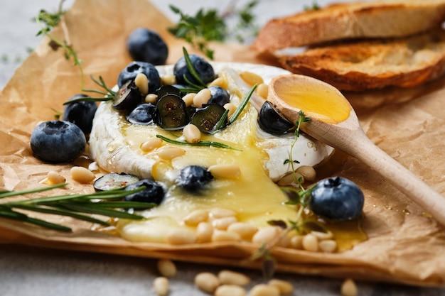 향신료 클로즈업으로 구운 카망베르. 치즈는 꿀, 잣, 블루베리와 함께 제공됩니다. 축제 미식가 와인 스낵.