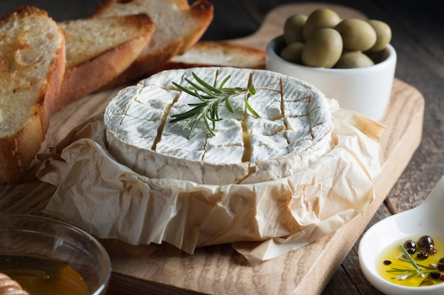Camembert and brie cheese on wooden  with tomatoes, letuce and garlic. italian food. dairy products.