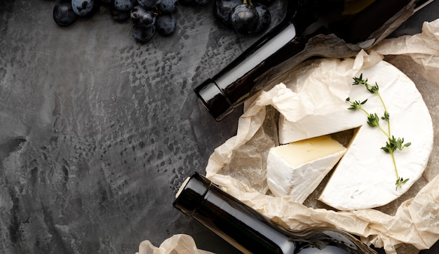 Camembert brie herbs , grapes. restaurant dinner, wine tasting on dark concrete background. long web banner. red wine bottle cheeses grapes. vintage still life wine composition with aged cheese